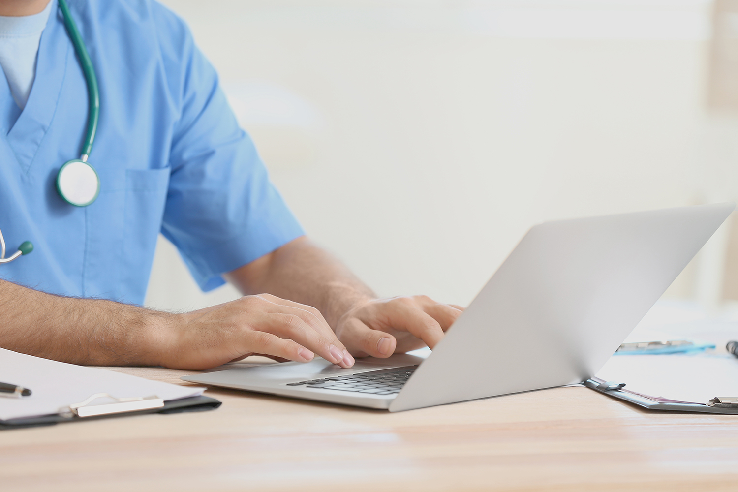 Young male doctor working on laptop in clinic, closeup